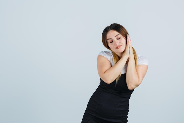 Giovane donna che si appoggia la guancia sui palmi e sembra assonnata