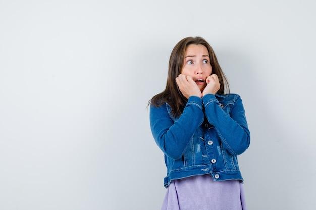 Giovane donna che si appoggia le guance sulle mani in maglietta, giacca e sembra terrorizzata, vista frontale.