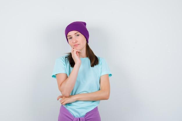 Giovane donna che si appoggia il mento a portata di mano in maglietta blu, berretto viola e sembra seria, vista frontale.