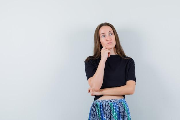 Giovane donna appoggiata sul mento e pensando a qualcosa in maglietta nera e gonna blu e guardando pensieroso