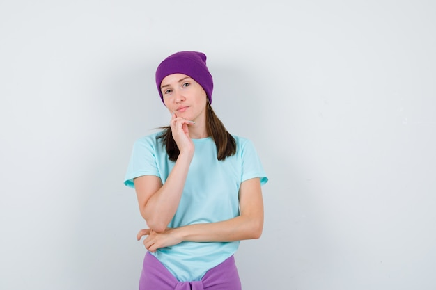 파란색 티셔츠, 보라색 비니를 입은 젊은 여성이 손에 턱을 기대고 진지하게 앞을 바라보고 있습니다.