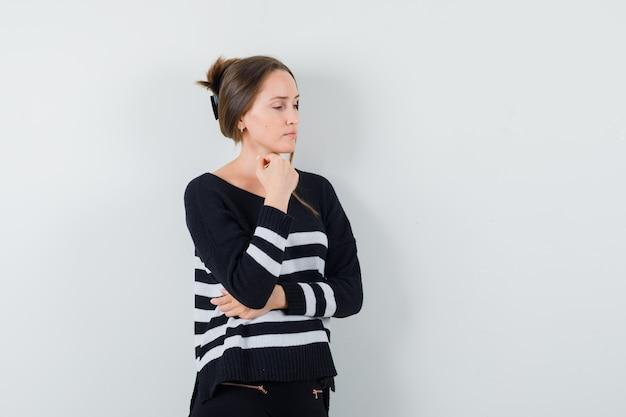 手のひらに顎をもたれ、縞模様のニットと黒のズボンでポーズを考えて立っている若い女性
