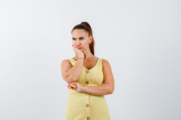 Giovane donna che si appoggia sul mento con il palmo in abito giallo e guardando sconvolto, vista frontale.