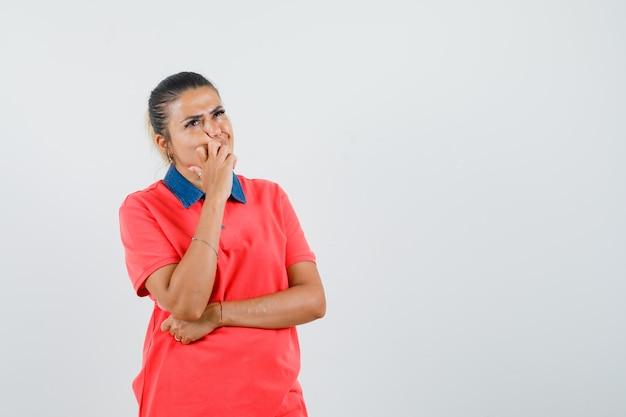 Giovane donna che si appoggia la mano sulla bocca, in piedi nel pensiero posa in maglietta rossa e guardando pensieroso. vista frontale.
