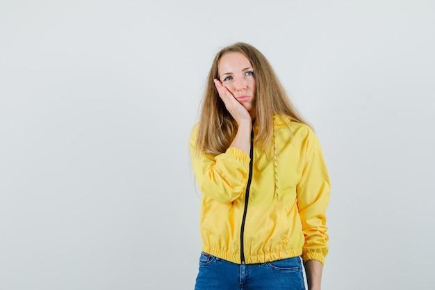 Giovane donna che si appoggia le mani sulla guancia in bomber giallo e jeans blu e guardando dispiaciuto. vista frontale.
