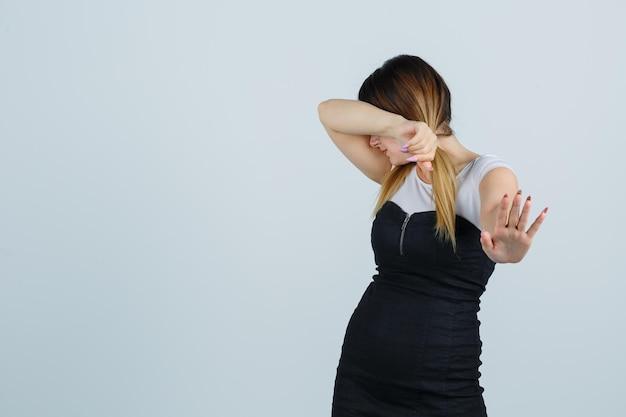 Giovane donna che si appoggia la testa sul gomito mentre mostra il gesto di arresto