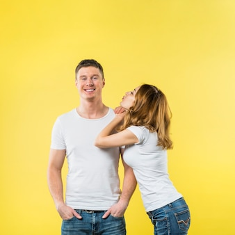 Young woman leaning on her boyfriend's shoulder blowing kiss against yellow backdrop