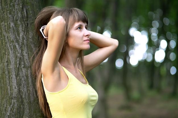 大きな木にもたれて若い女性