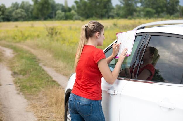 차에 기대어 지도를 보고 있는 젊은 여성