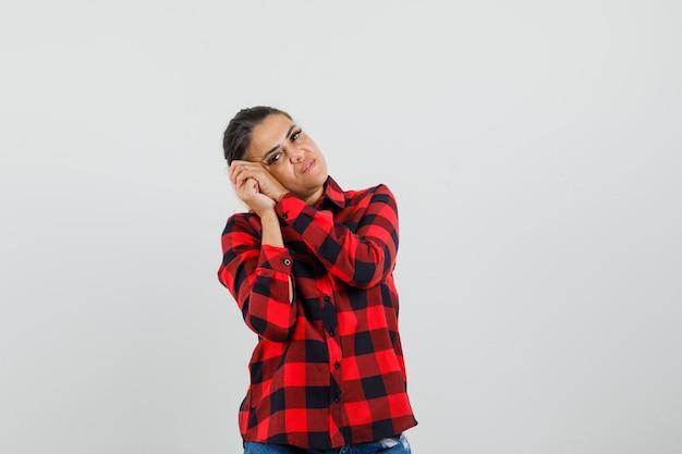 チェックシャツ、ショートパンツ、正面図の枕として握りしめられた手に寄りかかって若い女性。