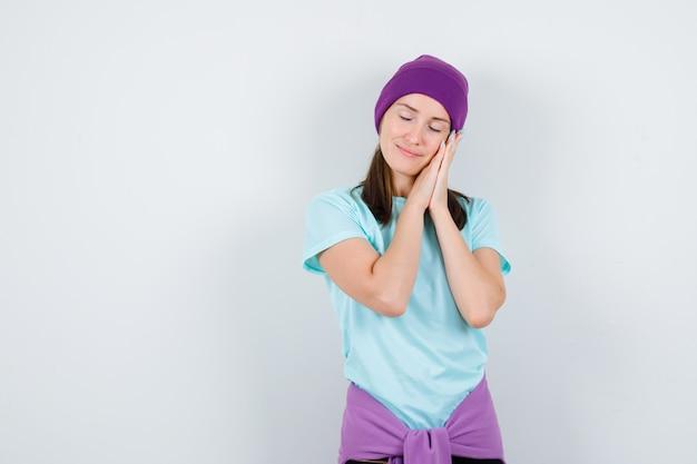 Tシャツ、ビーニーの枕として手のひらに寄りかかって、平和に見える若い女性。正面図。