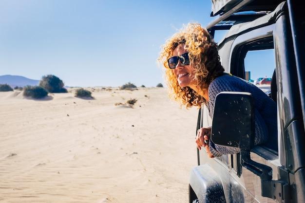 車の窓の外に寄りかかって自然を見ている若い女性。休暇旅行を楽しんでいる美しい女性。砂の上で自然を探索する車の窓から外を眺める女性