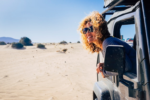 Young woman leaning outside car window and looking at nature. beautiful woman enjoying holiday trip. woman looking out from car window exploring nature on sand