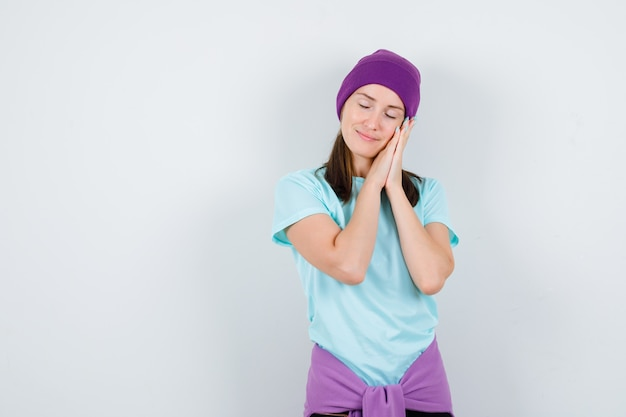 Young woman leaning on palms as pillow in t-shirt, beanie and looking peaceful. front view.