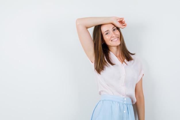 Giovane donna pendente braccio alzato sulla testa in t-shirt, gonna e che sembra felice. vista frontale.