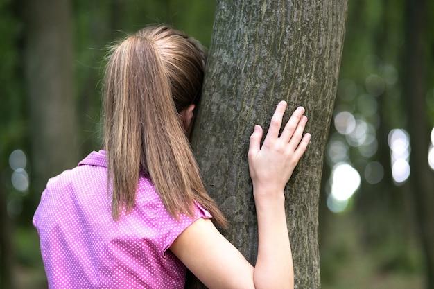 夏の森で彼女の手でそれを抱き締める木の幹に寄りかかっている若い女性。