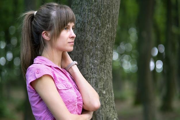 夏の森の木の幹に寄りかかって若い女性。
