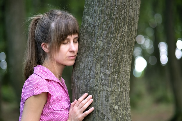 Young woman leaning to tree trunk hugging it with her hands in summer forest.