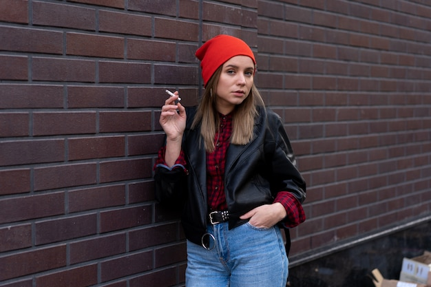 Young woman in leather jacket smoking