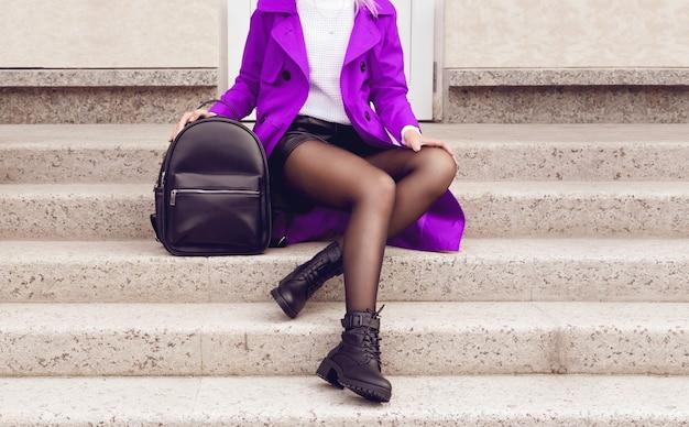 Ноги молодой женщины в черных ботильонах и фиолетовом пальто с сумкой. модный хипстерский наряд