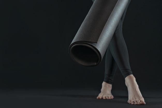 暗い黒の背景にヨガとヨガのマットを練習する若い女性の足。コピースペース。