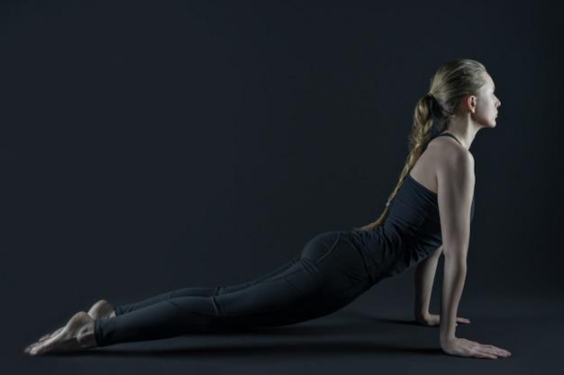 Молодая женщина ноги практикующих коврик для йоги и леггинсы