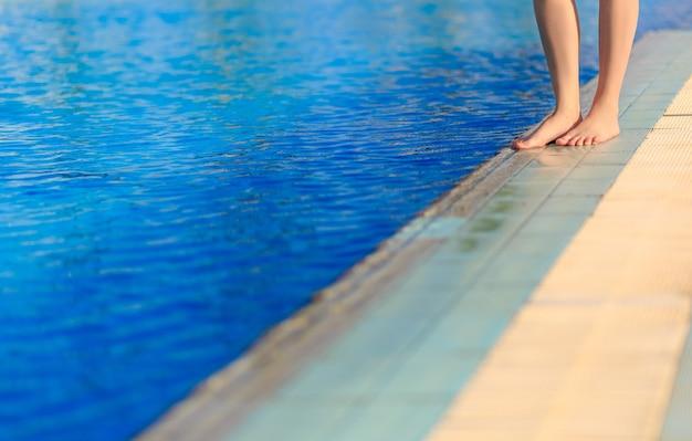 スイミングプールの国境の正面に立っている若い女性の足