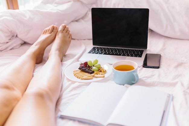 Young woman legs. tea at home in her bed, checking her laptop, reading a book and having breakfast.