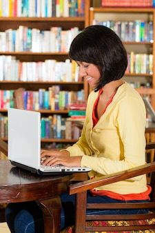 Young woman in a library, writes on laptop learning