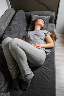 Young woman lies on bed with stomachache