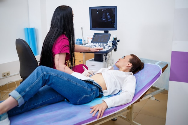A young woman lies on a couch, a doctorã¢â€â™s appointment, an ultrasound scan of the abdominal organs is performed on the girl, the doctor examines the patient