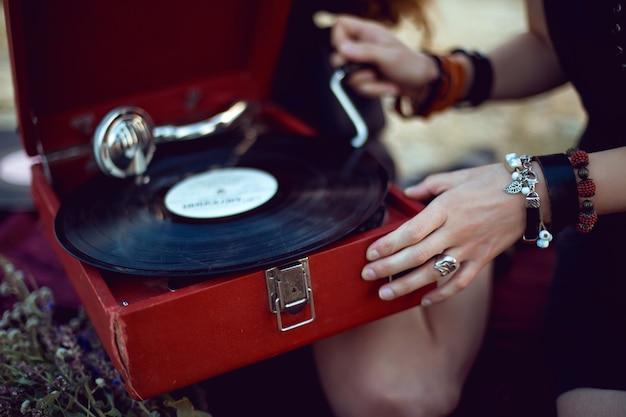 Молодая женщина лежит на природе в черном платье рядом со старым граммофоном и слушает музыку