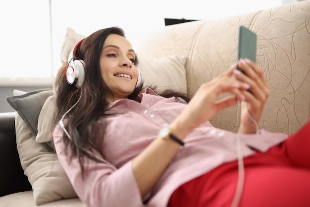 Молодая женщина лежит на диване в наушниках и смотрит в смартфон