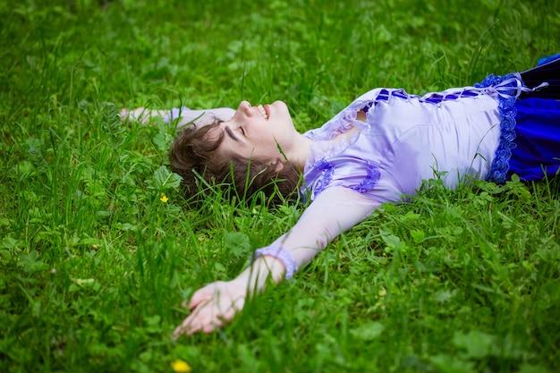 젊은여자가 하루를 즐기는 푸른 잔디에 누워