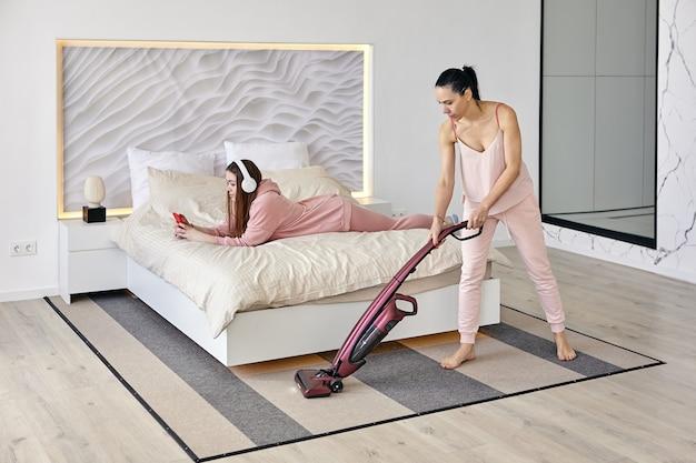 Молодая женщина лежит на животе и слушает музыку, в то время как ее мать чистит пол пылесосом.