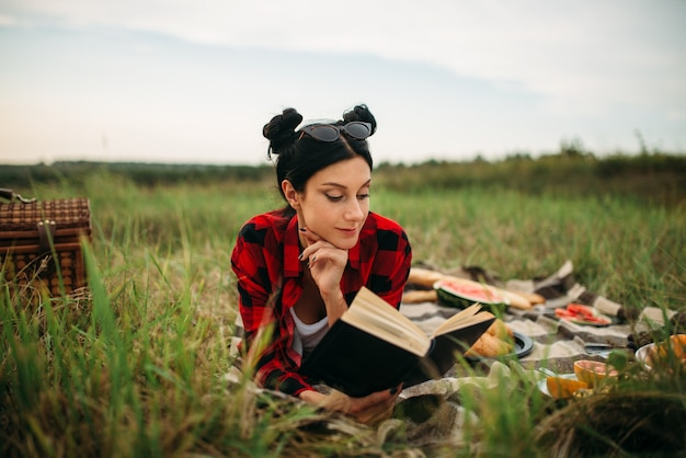 Young woman lies on plaid and reads book, picnic in summer field. romantic junket, happy holiday