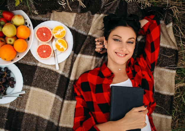 Young woman lies on plaid, top view, picnic in summer field. romantic junket, happy holiday