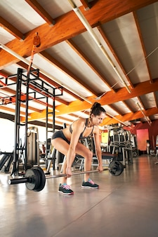 Young woman lifting barbells looking focused, working out in a gym alone.