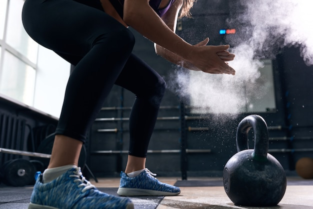 Young woman lifting kettlebells in crossfit gym