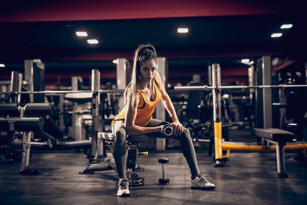 Young woman lifting weights and sitting on bench while looking at camera. side light, gym interior.