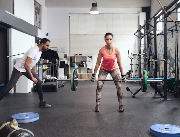 Young woman lifting weights with a look of effort. her coach, a young man with a beard, is beside her controlling her posture to avoid injury