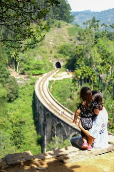 A young woman in a light dress with her daughter looks at the nine-arch bridge in sri lanka.