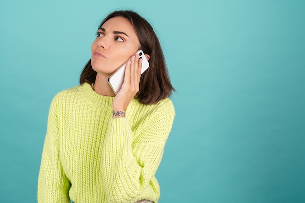 Young woman in light green sweater with mobile phone having conversation listening audio message