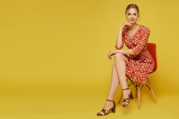 A young woman in a light summer dress with a floral pattern sitting on the chair over yellow wall, isolated