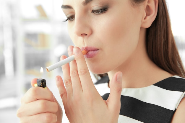 Young woman lighting cigarette at home