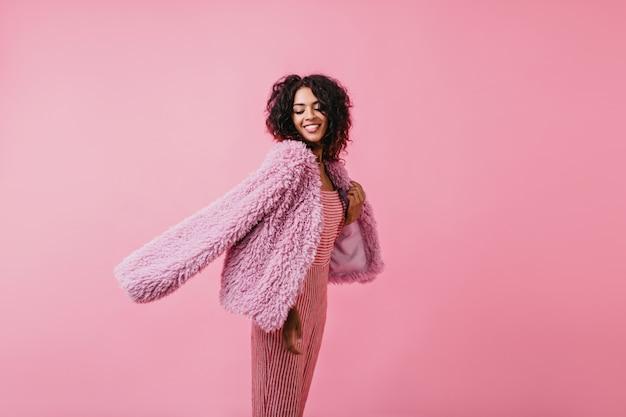 Giovane donna in giacca di pelle di pecora color lilla posa con gioia con un dolce sorriso. ritratto di bellissima modella in abiti alla moda.