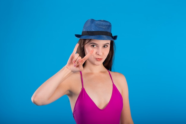 Young woman in lilac swimsuit lingerie and hat with hand gestures isolated on blue