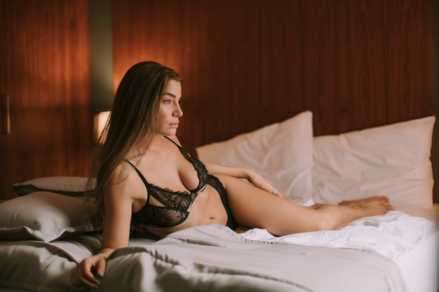 Young woman in lingerie lying on the bed