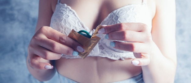 Young woman in lingerie opens a condom