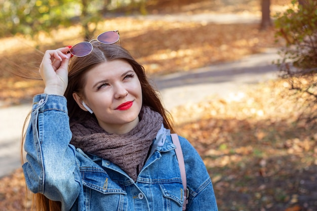 Young woman listen to music in an autumn park
